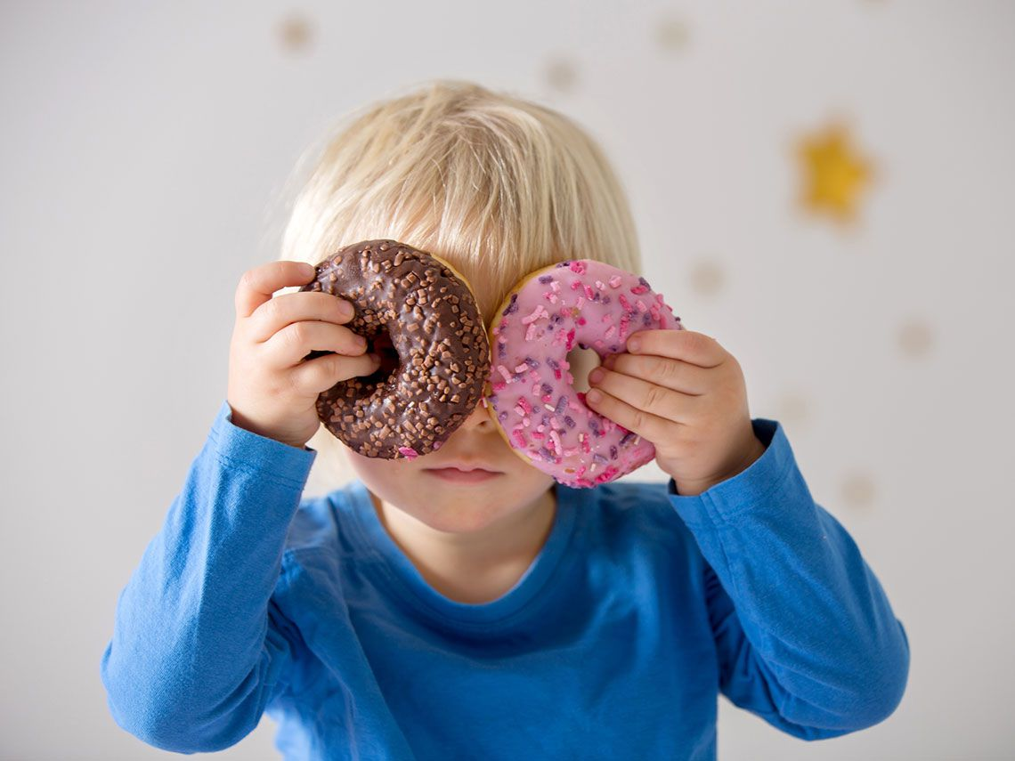 niño desayunando dos donuts