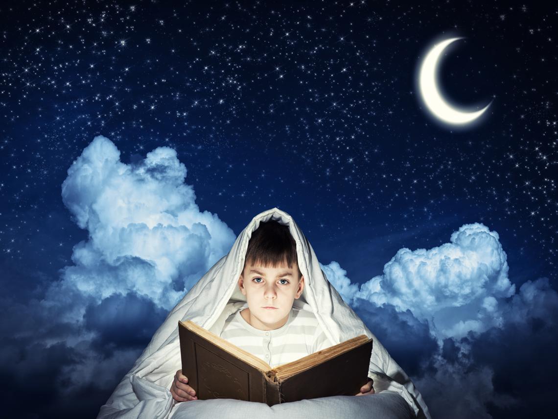 Niño leyendo sobre fondo lunar