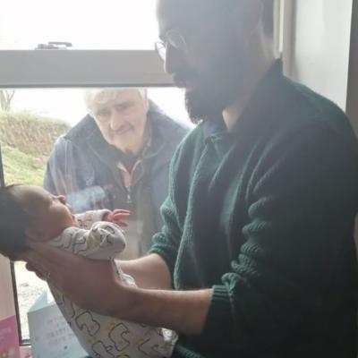 La foto que se ha hecho viral de un abuelo conociendo a su nieto a través del cristal de la ventana por culpa del coronavirus