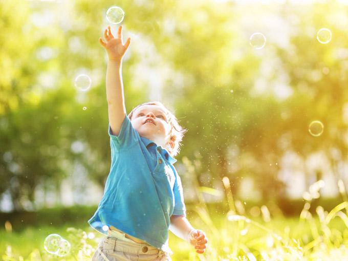 niño jugando con pompas