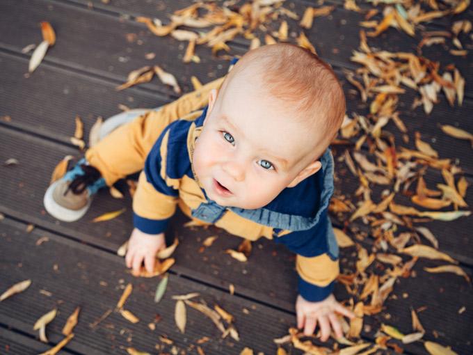 niño jugando con hojas